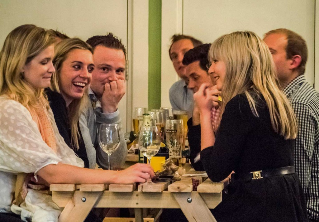 People drinking, talking and laughing in a pub in london