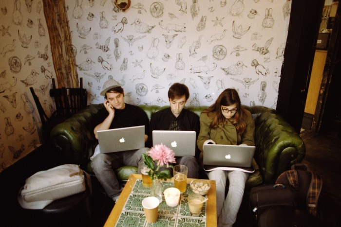 people on their laptops in a London flat